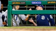 San Diego Padres' Eric Hosmer, left, is greeted by bench coach Mark McGwire after scoring on a hit by Franchy Cordero during the sixth inning of a baseball game against the Pittsburgh Pirates, Friday, May 18, 2018, in Pittsburgh. (AP)