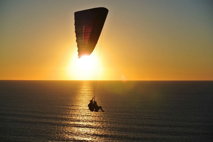paragliding into sunset bali