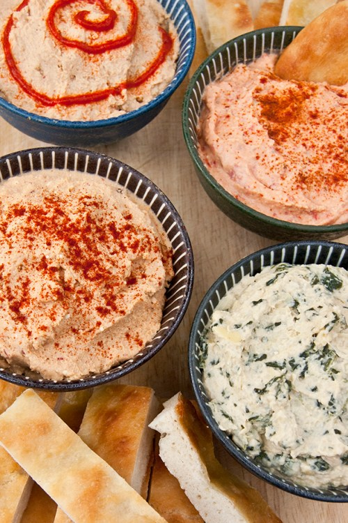 A hummus flight is perfect for your next party or potluck. Get the recipes for chipotle feta hummus, spinach artichoke hummus, roasted red pepper hummus, and spicy hummus