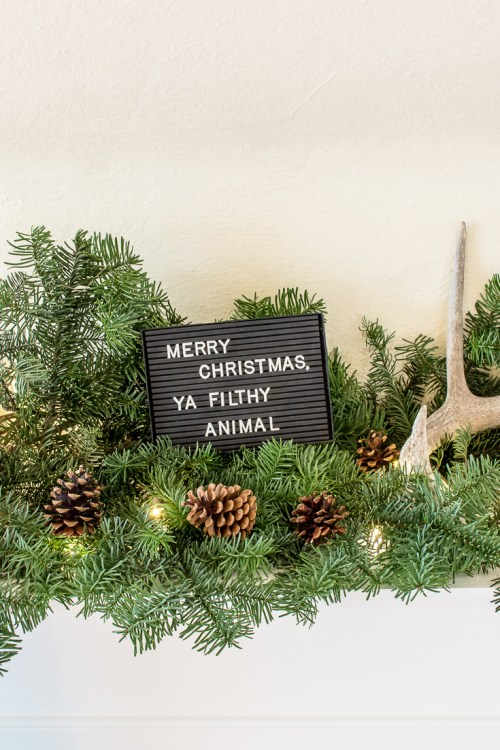 Never decorated a mantel for Christmas before? Neither had I, but it's easy! Keep your Christmas mantel simple with greenery, lights, and a few accessories. #Christmas #decor #mantel