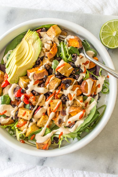 Roasted sweet potatoes and black beans topped with a creamy cashew lime dressing make this vegan salad refreshing and satisfying. #vegan #salad #lunch