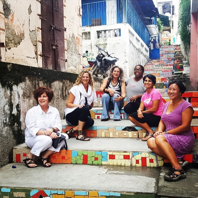 Sitting on the mosaic stairs in Jacmel with fellow travel companions