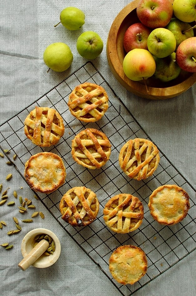 Mini cardamom and cinnamon spiced apple hand pies baked in a muffin tin, perfect for thanksgiving or Christmas