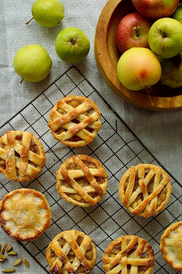 Mini apple hand pies baked in a muffin tin spiced with cardamom and cinnamon