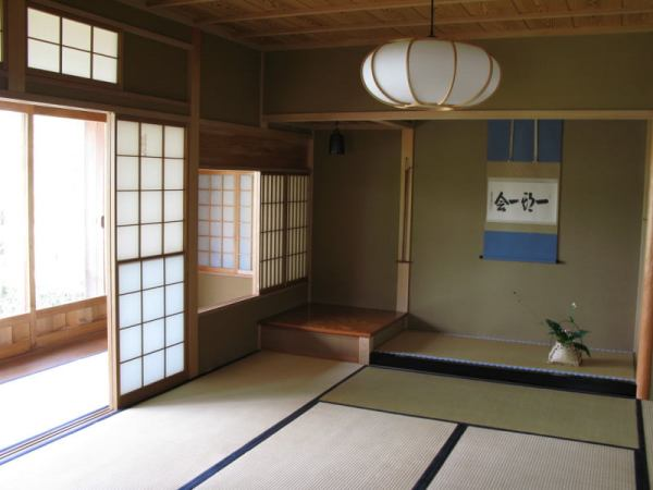 interior-japanese-traditional-decoration-living-room-with-green-wall-mounted-light-beige-carpet-floor-pendant-sliding-doors-and-wooden-roof-picture-flower-pots-modern-japanese-small-house-inter