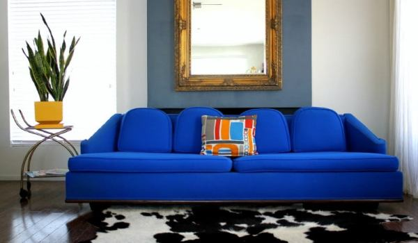 The-awesome-electric-retro-blue-sofa-with-four-pillows-in-blue-and-white-living-room-with-artistic-mirror-and-laminate-wood-flooring-charm-blue-sofa-Furniture-in-the-living-room