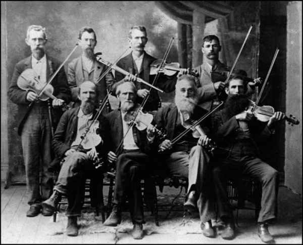 Eight fiddlers, one with a walking stick fiddle.