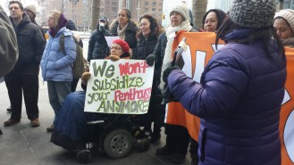 Approximately a dozen people looking off camera, a woman in a wheelchair is carrying a sign with a message (see title)