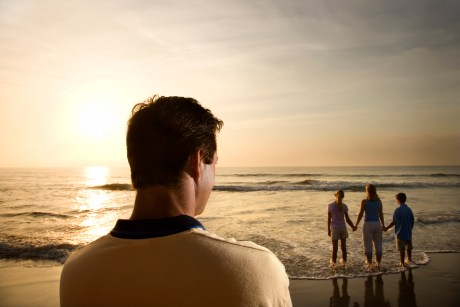 Man watching family at beach