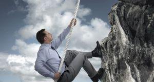 Businessman climbing mountain