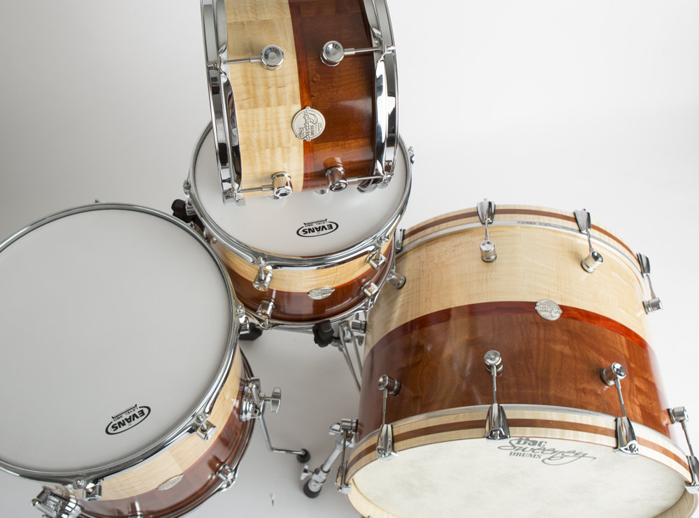 "Doc Sweeney showed its Dual Species kit (22"" x 15"", 16"" x 15"", 13"" x 9"", and 12"" x 8"") at Winter NAMM 2017. The shells, which are .25"" thick with milled reinforcing rings, feature a hand rubbed oil finish and combine Tiger Maple and figured Makore with Redheart band."