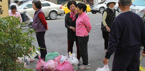 photo credit: People wait outside to deposit their trash bags. via photopin (license)
