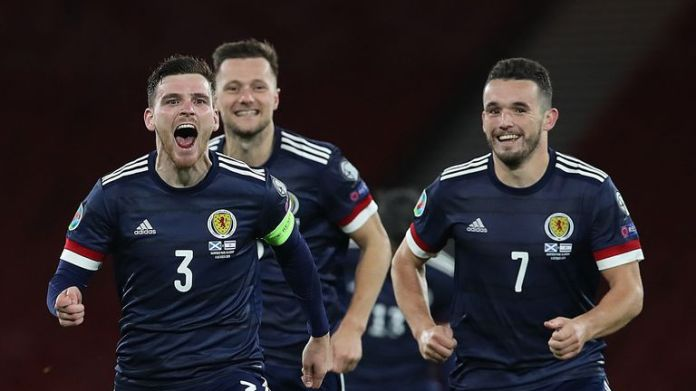 Andy Robertson, Liam Cooper and John McGinn celebrate Scotland's dramatic penalty shootout victory