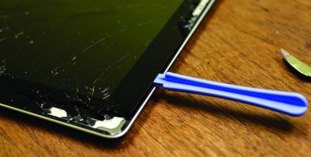Una pry tool separando la pantalla rota de una ultrabook de su carcasa para poder desmontarla sin que se vuelvan a encastrar.