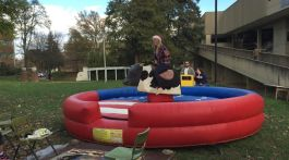 Taylor Joyce riding the mechanical bull for a department of mass communication fundraiser. (Photograph by Emma Hammer/East Tennessean)