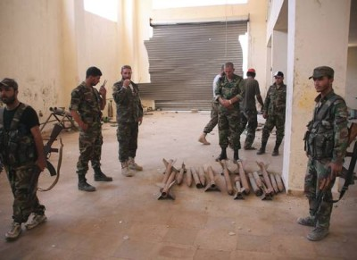 Forces loyal to Syria's President Bashar al-Assad stand by weapons at a weapons factory which they said were used by rebels in Aleppo's Sheikh Najjar Industrial City after claiming to have regained control of the area