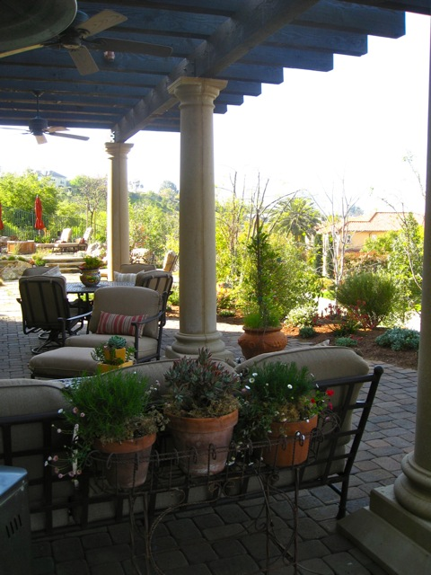 Potted plants divide areas of the patio into intimate spaces