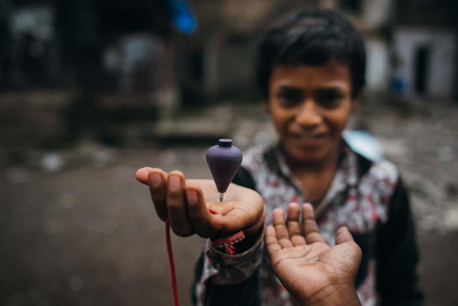 Zwei Jungen spielen in den Slums von Mumbai mit einem Spielzeugkreisel.