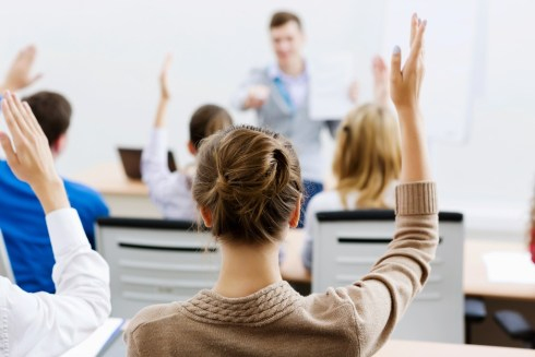 A woman raising her hand in a classroom of employees