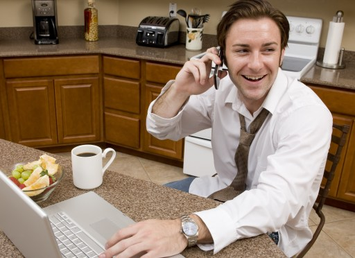 A young businessman talking on his phone while eating his morning breakfast