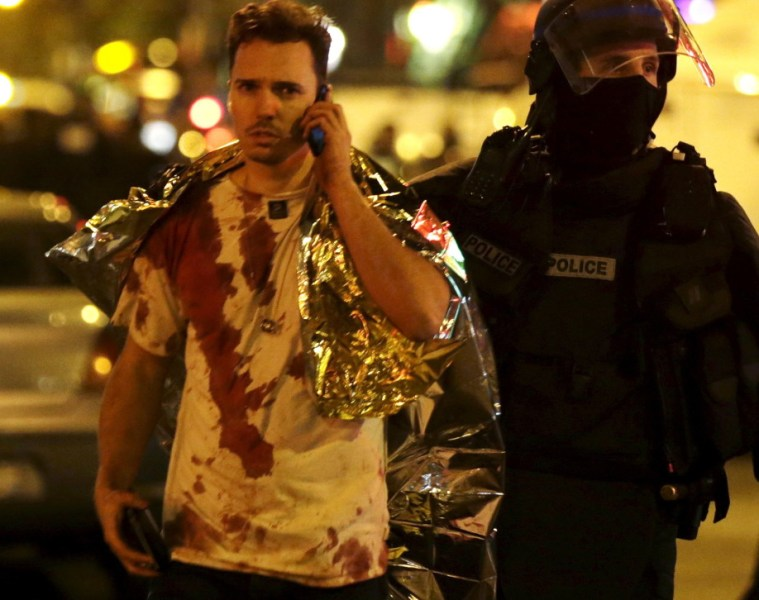 A French policeman assists a blood-covered victim near the Bataclan concert hall following attacks in Paris, France