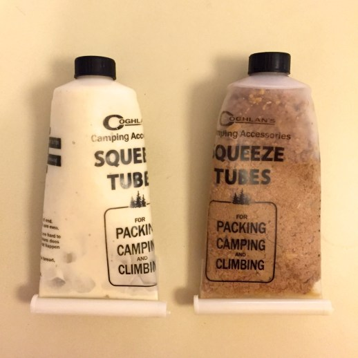 Two Coghlan's food tubes used for dog training. They are clear plastic with black caps and a white clamp at the bottom. The one on the left has a white filling (Neufchatel cheese, milk, and peanut butter) and the one on the right has a brown filling: canned cat food.