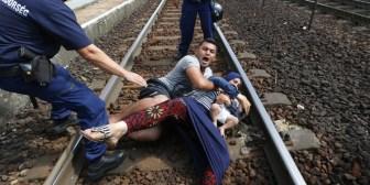 Refugiados sirios se aferran con un bebé a las vías del tren para evitar que los deporten