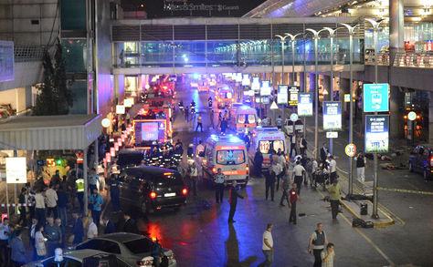 Esta imagen obtenida de la agencia de noticias Ilhas muestra ambulancias y policías creando un perímetro, al lado de gente tirada en el suelo (der.), después de dos explosiones seguidas de disparos en el mayor aeropuerto de Turquía en Istabul.