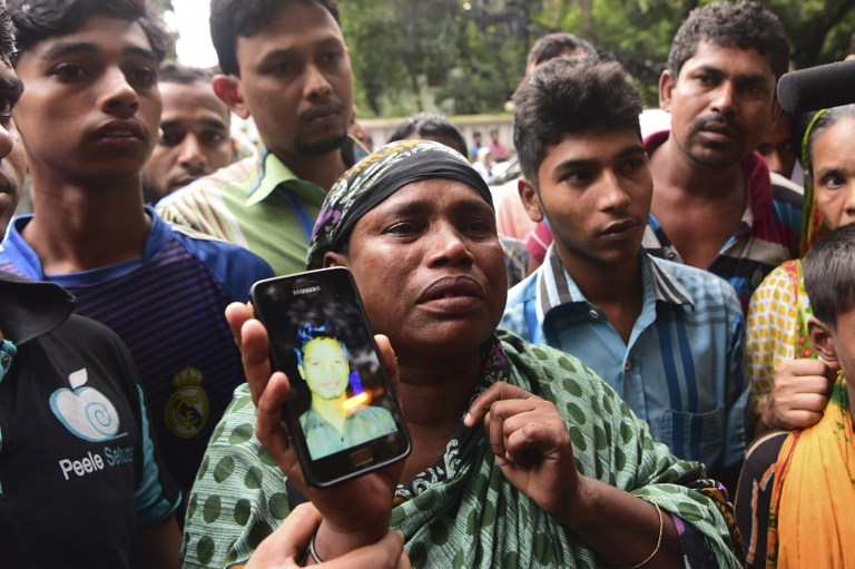 """A Bangladeshi woman holds a photograph of her son, who worked at a cafe that was the scene of an attack and seige, and who is missing, in Dhaka on July 3, 2016. Bangladesh said July 3 the attackers who slaughtered 20 hostages at a restaurant were well-educated followers of a homegrown militant outfit who found extremism """"fashionable"""", denying links to the Islamic State group. As the country held services to mourn the victims of the siege in Dhaka, details emerged of how the attackers spared the lives of Muslims while herding foreigners to their deaths. / AFP PHOTO / APF / STR"""