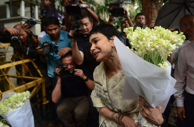 A woman speaks before leaving a floral arrangement at a road block leading to an upscale cafe that was the scene of a bloody attack in the Bangladesh capital Dhaka on July 3, 2016. Bangladesh began observing two days of national mourning July 3 after 20 hostages were slaughtered at a restaurant packed with foreigners in a terrifying escalation of a campaign of attacks by Islamist extremists. Seven Japanese nationals were killed in the attack. / AFP PHOTO / STR