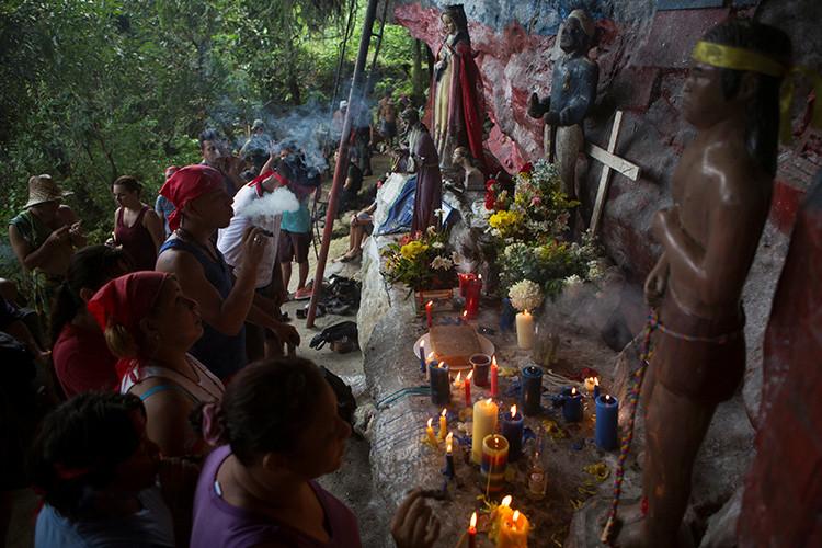 Los devotos rezan, fuman puros y encienden velas en el santuario de María Lionza en la montaña de Sorte en las afueras de Chivacoa , en el estado de Yaracuy