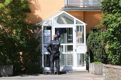 Un miembro del cuerpo de policía se sitúa frente a la casa de acogida que alojaba al afgano de 17 años solicitante de asilo, en Ochsenfurt, Alemania./ EFE
