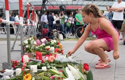 Homenaje. Una joven deja flores en recuerdo de las víctimas, frente al shopping donde el viernes un atacante disparó y dejó nueve muertos. /AP