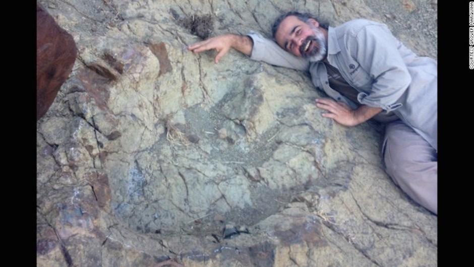 El paleontólogo Sebastián Apesteguia posa junto a la inmesa huella fosilizada. (Crédito: Grover Marquina).