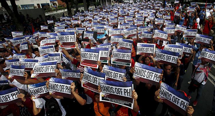 Activistas con carteles en los que puede leerse 'manos fuera de Filipinas' durante las protestas por las tensiones en el mar de la China Meridional frente al consulado chino en Gran Manila.