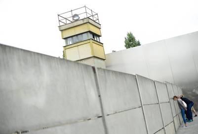 Espiando. Un grupo de personas se asoma a través de un pequeño hoyo en el memorial del Muro de Berlín en Bernauer Strasse, en el 55 aniversario de su construcción. /AFP