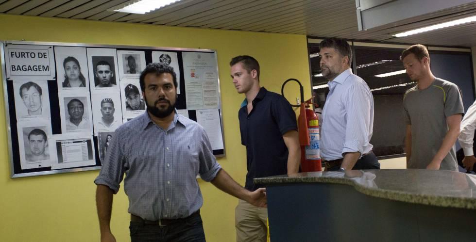 Los deportistas Gunnar Bentz, segundo por la izquierda, y Jack Conger, cuarto por la derecha, dejan las dependencias policiales del aeropuerto de Río.