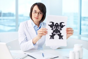 Serious psychologist showing paper with Rorschach inkblot