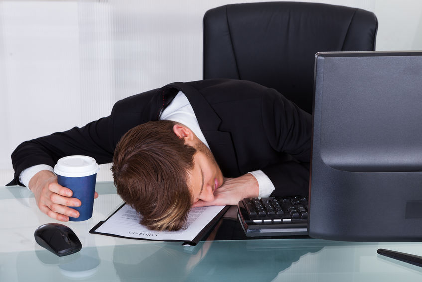 28322729 - overworked businessman holding disposable coffee cup while resting on contract paper at office desk