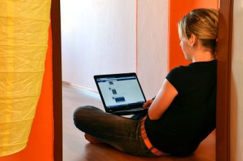 55061768 - bytca, slovakia - april 27, 2012: young woman browses her facebook page on laptop seated on the floor