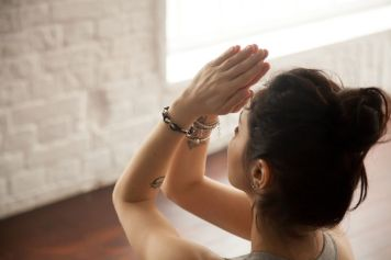 75178736 - young attractive yogi woman practicing yoga concept, doing namaste gesture, namaste hands to forehead, working out, wearing wrist bracelets, studio background, closeup, view over the shoulder