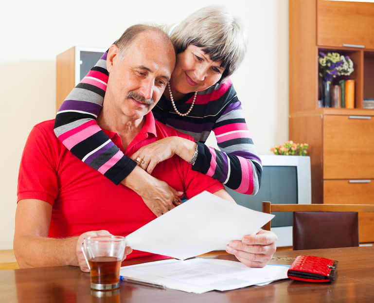 25089515 - serious mature couple looking financial document at home interior