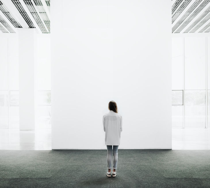 46776009 - young woman walking through on the exhibition hall and examines the gallery
