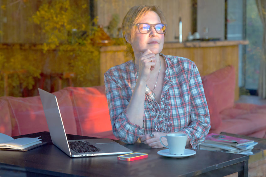 Middle Age Woman discovering new Ideas for her Freelance Project sitting at Table with Computer and Coffee Mug in cozy Home Interior