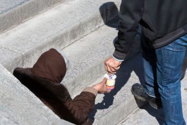 A man is giving money to a homeless female begger who is begging at the subway underpass stairs in the center of Sofia.