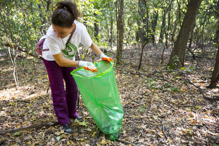 Sofia, Bulgaria - 16 September, 2017: Woman picks up trash in the forest participating in a cleaning campaign. Ecology person cleaning the park.