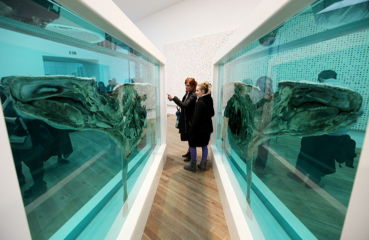 Visitors look at Damien Hirst's piece 'Death Explained'