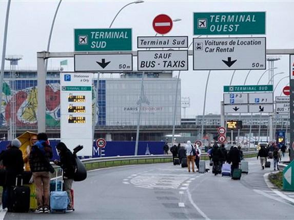 Viajeros caminando por la autopista que llega al aeropuerto de Orly, al sur de París, el sábado 18 de marzo de 2017. Un hombre murió baleado en el aeropuerto tras intentar arrebatar su arma a un soldado que protegía el lugar, según la policía, lo que provocó una evacuación parcial de la terminal. (AP Foto/Thibault Camus)