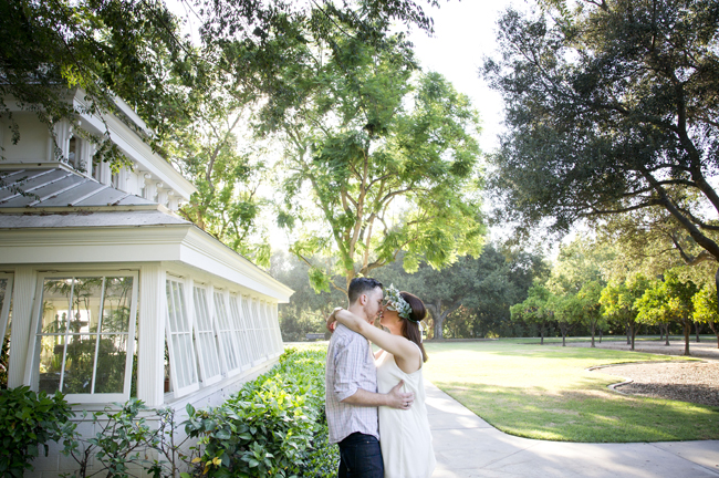 couple kiss outside greenhouse at Santa Fe Springs engagement session