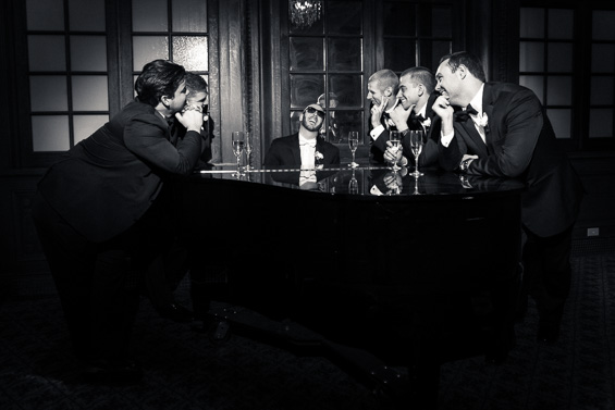 fun photo of groom playing piano surrounded by groomsmen - photo: Daniel Fugaciu Photography | via http://emmalinebride.com